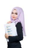 举行报告的美丽的现代年轻亚裔回教女商人 免版税图库摄影