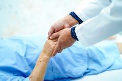 举行接触的医生手有爱,关心的亚裔资深或年长老妇人妇女病人,帮助,鼓励和同情 库存图片