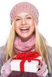 举行提出的冬天帽子和围巾的笑的女孩箱子 库存照片