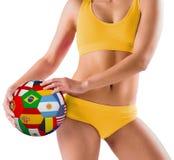 举行旗标橄榄球的黄色比基尼泳装的适合的女孩 免版税库存照片