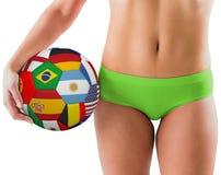 举行旗标橄榄球的绿色比基尼泳装的适合的女孩 免版税图库摄影
