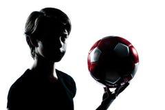 举行显示的一个少年男孩女孩剪影足球footba 免版税库存照片