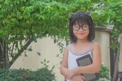举行智能手机和微笑的玻璃的逗人喜爱的矮小的亚裔中国女孩 免版税库存照片