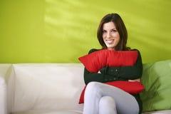举行枕头和微笑的愉快的妇女画象 图库摄影