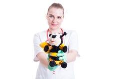 举行模糊的长毛绒玩具和微笑的年轻儿科医生 免版税库存图片