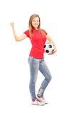 举行橄榄球的俏丽的女孩 免版税库存图片