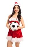 举行橄榄球的圣诞老人成套装备的妇女 免版税图库摄影