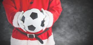 举行橄榄球的圣诞老人的综合图象 免版税图库摄影