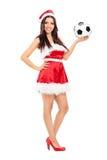 举行橄榄球的女性圣诞老人 免版税库存照片