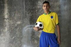 举行橄榄球的成套工具的年轻巴西足球运动员 免版税库存照片