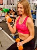 举行橙色哑铃的红色的女孩入体育健身房 免版税库存照片