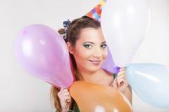 举行气球和微笑的生日盖帽的深色的妇女 免版税库存照片