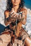 举行沙子关闭在海滩的美好的年轻女人手 免版税库存照片