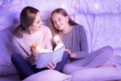 举行火炬和读的微笑的母亲和女儿 库存照片