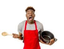 举行烹调的厨师围裙的年轻绝望和迷茫的黑人美国黑人的人罐和匙子在看起来他的手上丢失 免版税库存图片