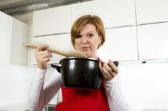 举行烹调的厨房的家庭厨师妇女罐和匙子在一张滑稽的令人厌恶的低级趣味面孔的品尝汤 免版税图库摄影