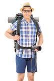 举行照相机和摆在的年轻男性远足者 免版税图库摄影
