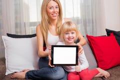 举行片剂和微笑的母亲和女儿 免版税图库摄影