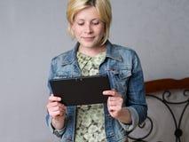 举行片剂和微笑的年轻白肤金发的妇女 免版税图库摄影