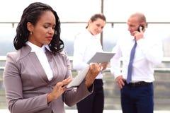 举行片剂手中常设室外的非洲女实业家商人 库存图片