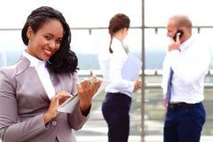 举行片剂手中常设室外的非洲女实业家商人 库存照片