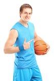举行球和打手势的一个微笑的蓝球运动员 免版税库存图片