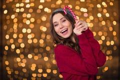 举行甜棒棒糖和微笑的快乐的可爱的少妇 免版税库存图片