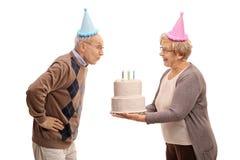 举行生日蛋糕和年长人吹的年长妇女 免版税库存图片