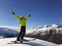 举行用手的愉快的滑雪者在山上面  免版税库存照片