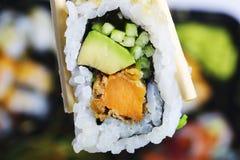 举行由筷子的寿司卷 日本烹调一个传统盘  免版税库存图片