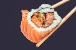 举行由筷子的寿司卷 日本烹调一个传统盘  库存照片