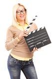 举行电影拍手的一个微笑的白肤金发的女性 免版税库存图片