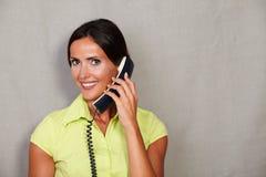 举行电话和微笑的美丽的深色的夫人 免版税图库摄影