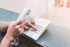 举行电话把柄和拨号的人的手 免版税图库摄影