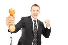 举行电话管和微笑的衣服的年轻人 免版税库存照片