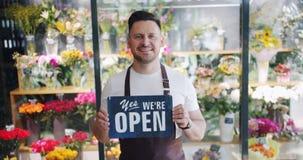 举行男性卖花人的慢动作我们是在花店的开放板岩身分 股票视频