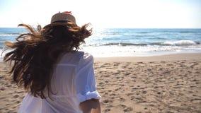举行男性手和赛跑在海滩的女孩对海洋 少妇跟我学射击帽子的拉扯她的男朋友 股票视频