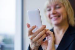 举行白色手机和微笑的妇女 特写镜头 免版税库存照片