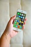 举行白色苹果计算机iPhone 5S的妇女 库存照片