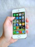 举行白色苹果计算机iPhone 5S的妇女 免版税库存图片