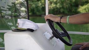 举行的上尉在有白色帽子的一条小船方向盘在手附近 与风船的夏时假期在开阔水域, 影视素材
