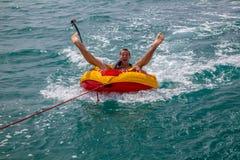 举行的人坐在一条小船拖曳的可膨胀的圆环在水中和做面孔对照相机和去赞成照相机 库存照片