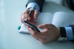 举行的人工作在办公室和保留他的电话 免版税库存照片