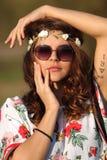 举行的太阳镜的性感的女孩嬉皮看照相机和递面孔户外 免版税库存图片