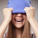 举行盖帽和微笑的女孩 免版税库存图片
