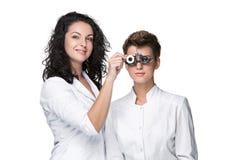 举行眼睛测试玻璃和给的验光师 免版税图库摄影