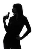 举行瞄准的性感的侦探妇女枪剪影 免版税库存图片