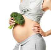 举行硬花甘蓝怀孕母性期望健康吃的美丽的孕妇大腹部 免版税库存照片