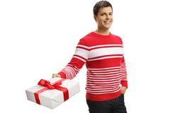 举行礼物盒和摆在的英俊的年轻人 免版税图库摄影