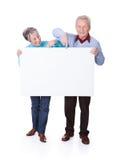 举行空白的招贴的资深夫妇 免版税库存图片